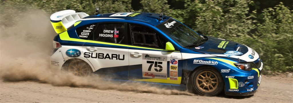 Subaru WRX STI at rally traveling on dirt path sporting decals from sponsors.